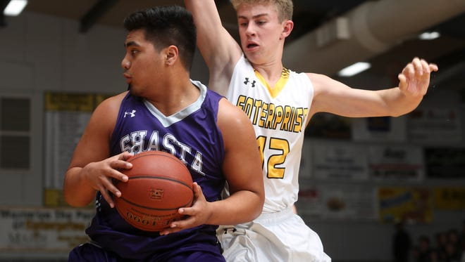 Shasta's Detrius Kelsall, left, controls the ball while Enterprise's Kristian Clements defends in their game Thursday night. Shasta edged Enterprise 61-59 at the Manatowa Gymnasium on Thursday night.