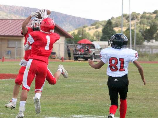 Cobre's Desi Montoya picks off this pass while Zeke Soliz helps him secure the ball. The Indains had two interceptions on Saturday's game against Mission Charter.