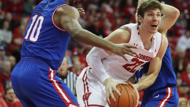 Wisconsin forward Ethan Happ attempts to pass between UMass-Lowell  guards Jahad Thomas (left) and Josh Gantz on Saturday at the Kohl Center.