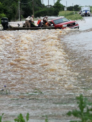 In this file photo, Texas game wardens rescue a man and a woman from a pickup washed off the road by swift-moving water on FM 1954 near Lake Arrowhead.