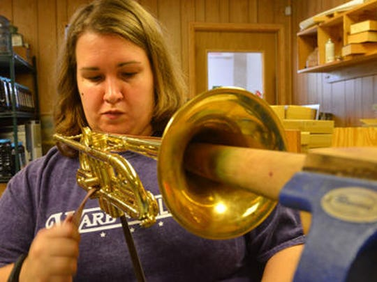 Kim Aubuchon meticulously had polishes a finished trumpet.
