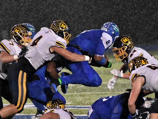 Kenny Mayberry (8) dives in for a Winton Woods first down while being pulled from behind by Moeller's Luke Szabados (4), Oct. 27, 2017.