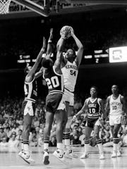 Kentucky center Melvin Turpin (54) attempts a jumper over the outstretched hands of Middle Tennessee State's Buck Hailey, left, and Chris Harris (20) at Vanderbilt's Memorial Gym on March 11, 1982.