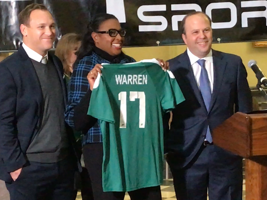 Jason Arnold of Capelli Sport, left, and Rhinos owner David Dworkin pose with Mayor Lovely Warren at Tuesday's announcement that Rochester's downtown soccer park will now be called Capelli Sport Stadium. The City of Rochester owns the facility. The Rhinos run it.