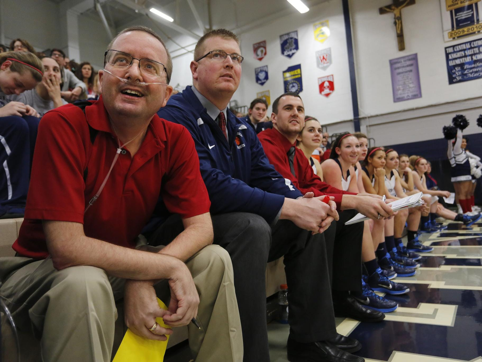 Central Catholic assistant girls basketball coach Jeff Dienhart, left, smiles as he watches the action with fellow assistant coaches Dave Crandall and Drake Barrett as the Knights host Guerin Catholic Friday, January 30, 2015, at Central Catholic Jr./Sr. High School. It was the first game for Dienhart in quite a while, as he had spent the better part of the month of January in the hospital. Dienhart is set to receive stem cell treatment in the Dominican Republic to hopefully assist in his battle with cystic fibrosis.