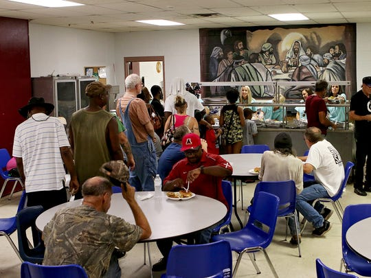 Volunteers with American National Bank help prepare hamburger plates with potato salad, beans and veggies at the Faith Mission Thursday.
