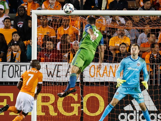 Seattle Sounders defender Will Bruin (17) scores past Houston Dynamo goalkeeper Joe Willis (31) during the first half of an MLS soccer match in the first leg of the Western Conference championship in Houston on Tuesday, Nov. 21, 2017. Seattle won, 2-0. (Brett Coomer/Houston Chronicle via AP)