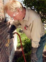Terminix technician Dan Creed applies pesticide at a home near Cincinnati.