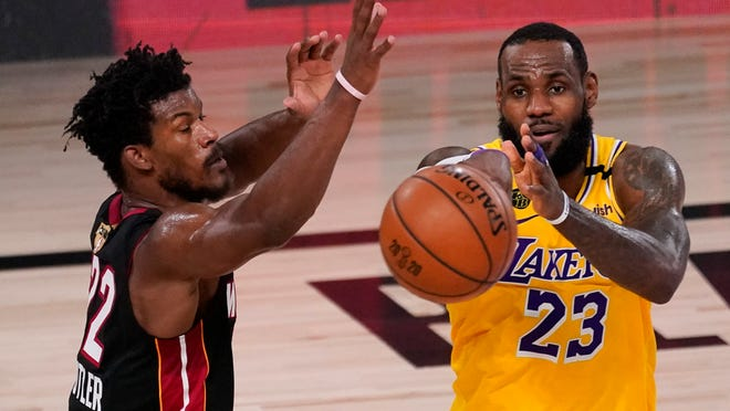 Lakers forward LeBron James, right, passes around Heat forward Jimmy Butler during the second half in Game 4 of the NBA Finals Tuesday night.