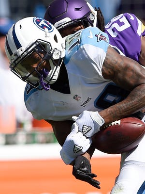 Titans wide receiver Tajae Sharpe (19) hangs on to a 15-yard catch as he is stopped by Vikings cornerback Trae Waynes (26) in the fourth quarter Sunday.