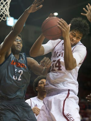 New Mexico State's Jose Campo grabs a rebound over Vaqueros Adonis Rwabigwi late in the second half Saturday night at the Pan American Center,