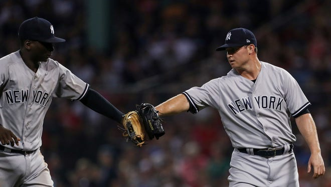 New York Yankees relief pitcher Zach Britton (53) (right) and shortstop Didi Gregorius (18) react after a great play by Didi Gregorius against the Boston Red Sox during the seventh inning at Fenway Park.