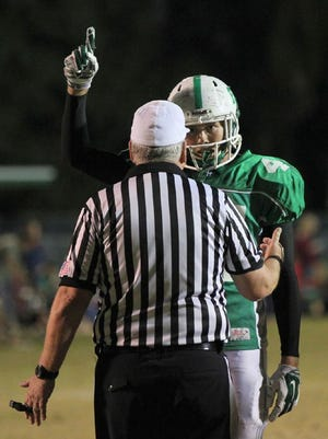 "Fort Myers High school football player Sam Turner questions a game official about the excessive celebration"" penalty he received after a post-touchdown prayer Friday."