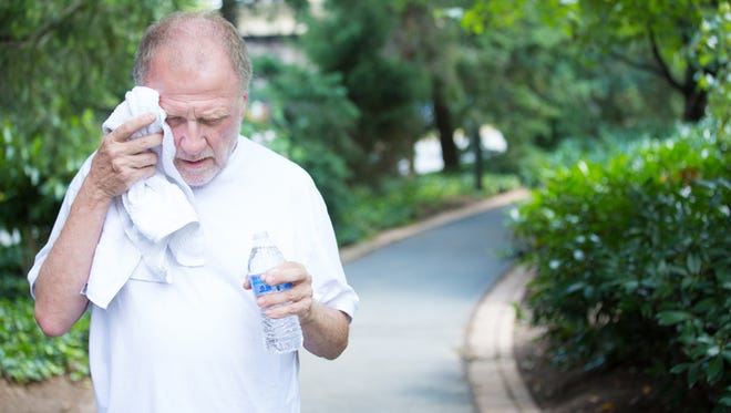Elderly man in white shirt having difficulties with extreme heat.