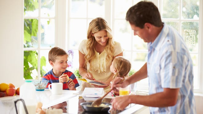 Father Preparing Food For His Family Making Them Breakfast In Kitchen