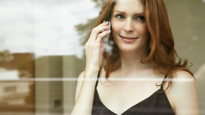 Young woman using mobile phone, smiling.
