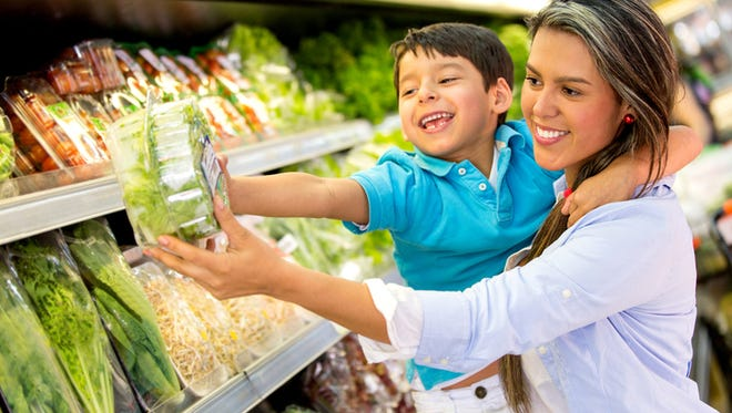 Woman at the supermarket with her son buying groceries
