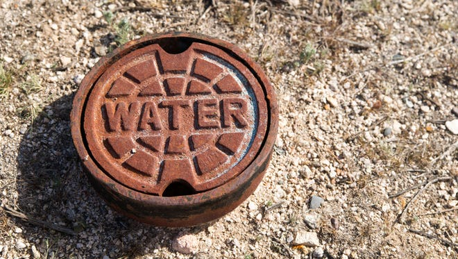 A rusted cast iron water main cover in the desert