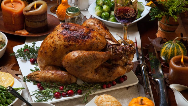 Roasted turkey garnished with cranberries on a rustic style table decorated with pumpkins, gourds, asparagus, Brussels sprouts, baked vegetables, pie, flowers, and candles.