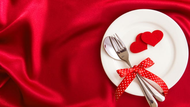 heart shape with White empty plate with fork and spoon on red silk fabric for love dinner concept