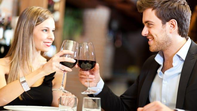 Couple toasting wine glasses in an elegant restaurant