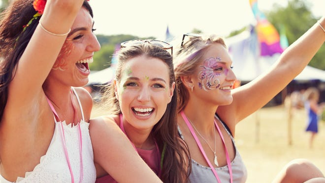Three girl friends at a music festival, one turned to camera