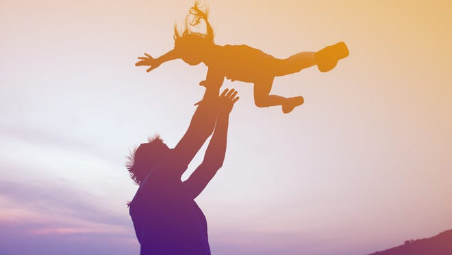 Silhouettes of happy family of father and daughter are having fun on sunset background. Father throws up daughter