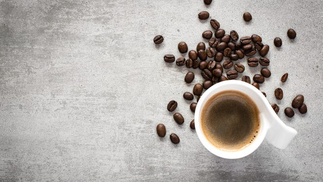 Cup of coffee and coffee beans on a gray concrete table with copy space