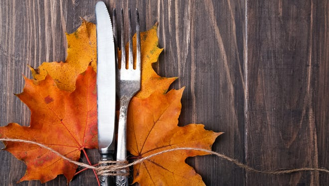 Knife, fork and yellow autumn leaves on the wooden table