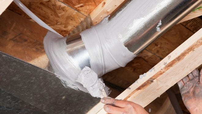 The caulk has been applied from a tube with a caulk gun and the brush is evenly spreading it over the joint.  Caulking residential ducts prevents air-conditioned or heated air from escaping the duct and prevents ambient air from entering the system. This is a new practice in home building to increase energy efficiency, eventually it may be come standard or mandatory.
