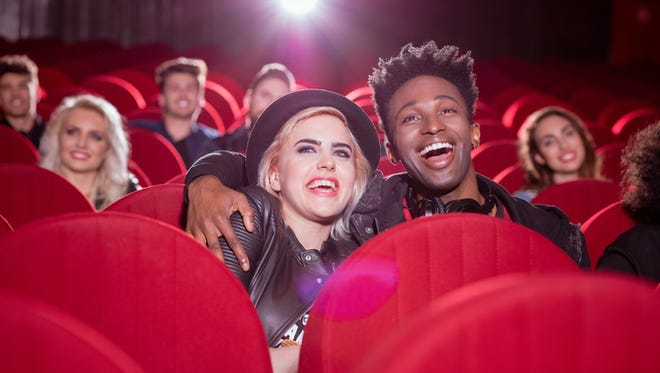 Group of happy young people in the movie theater, watching comedy. Focus on young couple - blonde girl and afro american guy.