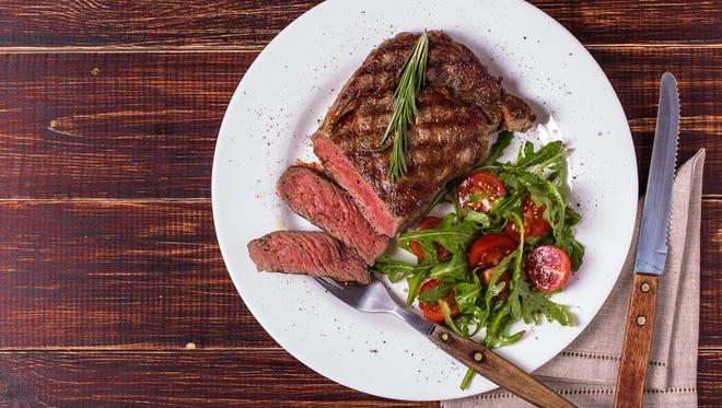 Ribeye steak with arugula and tomatoes on dark wooden background.