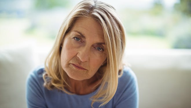 Portrait of sad senior woman sitting on bed at home