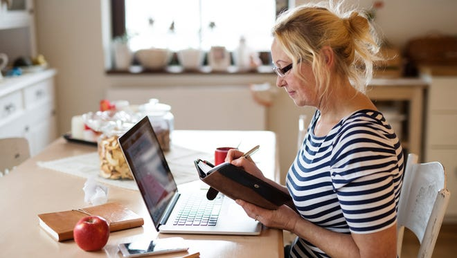 Woman with laptop at home at the kitchen table