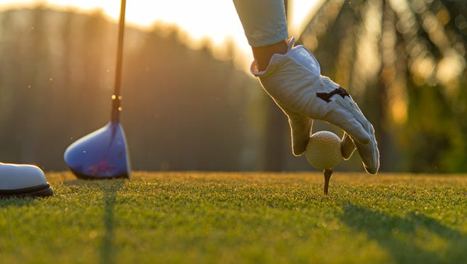 Woman putting golf ball on tee with club in golf course