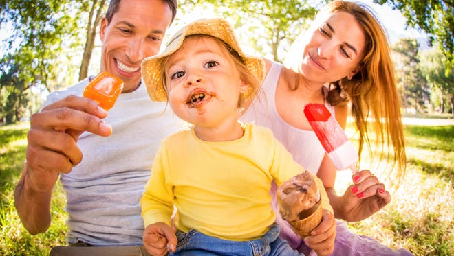 Smiling parents with their cute toddler who has ice cream messed on her face