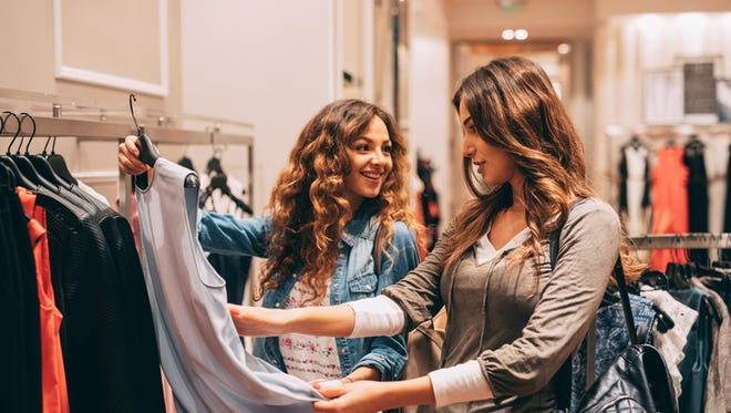 Two friends shopping in a clothing store.