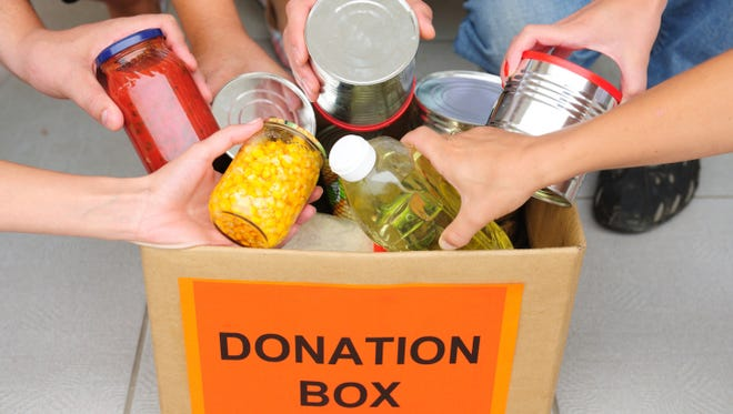 People putting food in a donation box.
