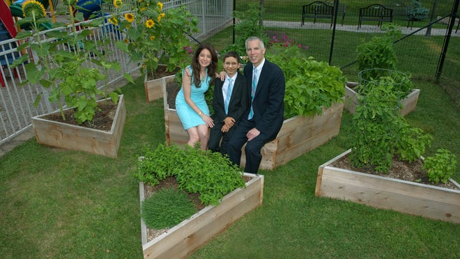 Sam Epstein, center, with mother, Lisa, left, and father, Sheldon, right, sit in the center section of the Mitzvah Garden that Sam created behind Adath Shalom synagogue in Morris Plains.