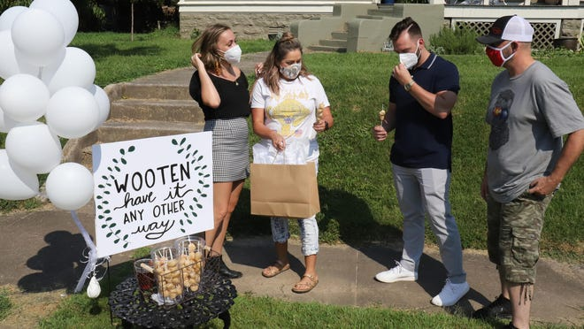 Jessye King, from left, Aimee Wooten, Coady Wooten and Jeremy Wooten wait to greet guest, Thursday, August 6, 2020, at Coady and Jessy's drive-thru-wedding shower in the Belle Grove Historic District on N 6th Street. King said that the COVID-19 pandemic caused the Fort Smith couple to change a few of the details of their August 8, 2020, wedding but it's not stopping them from getting married.