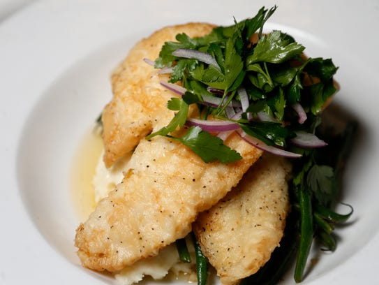 The sole meuniere is served with haricots verts, marcona