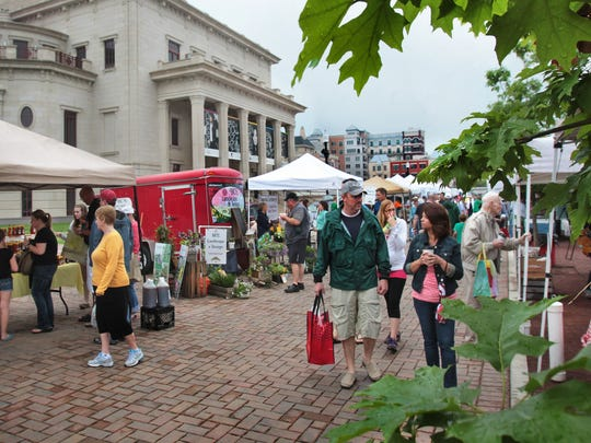 People walk through the Carmel Farmers Market during its opening day on May 18, 2013.