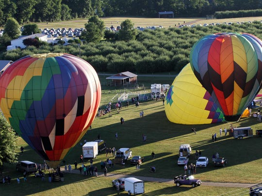 Balloons inflate as they prepare to take off Saturday