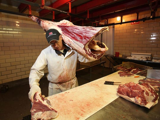 Kent Wiese carries a leg of beef into a cutting room at Amend Packing Co. in this 2015 file photo. The custom meat-cutting company closes Friday after 149 years in business.