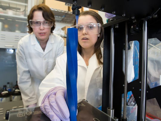 Jessica Sparks, associate professor of chemical, paper and biomedical engineering, with Katie Bootsma, master's student in chemical engineering, working with a 3D printer.