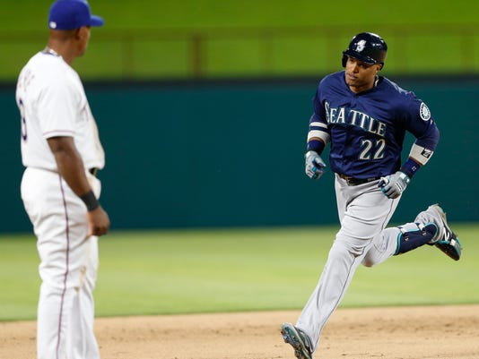 Seattle Mariners' Robinson Cano (22) circles the bases on his home run as Texas Rangers third baseman Adrian Beltre watches during the eighth inning of a baseball game, Tuesday, April 5, 2016, in Arlington, Texas. The Mariners won 10-2. (AP Photo/Jim Cowsert)