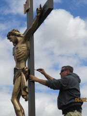 Chuck Schroedl tightens a bolt on the back side of the crucifix. The new crucifixion scene will be blessed by Jerome E. Listecki, Archbishop of Milwaukee Diocese, at the 175th anniversary celebration of St. John The Baptist Church in Johnsburg.