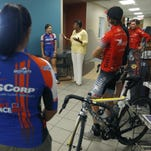 Gantt Recreation Center staffer Nate Smith asks kids to wish good luck to pro athletes competing in the Twilight Criterium on Saturday.