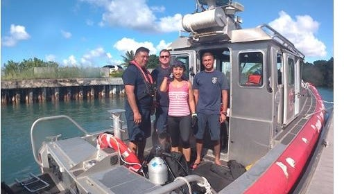 Kenneth and Angela Hunt, center, on a Guam Fire Department rescue boat after being pulled from the water Oct. 31