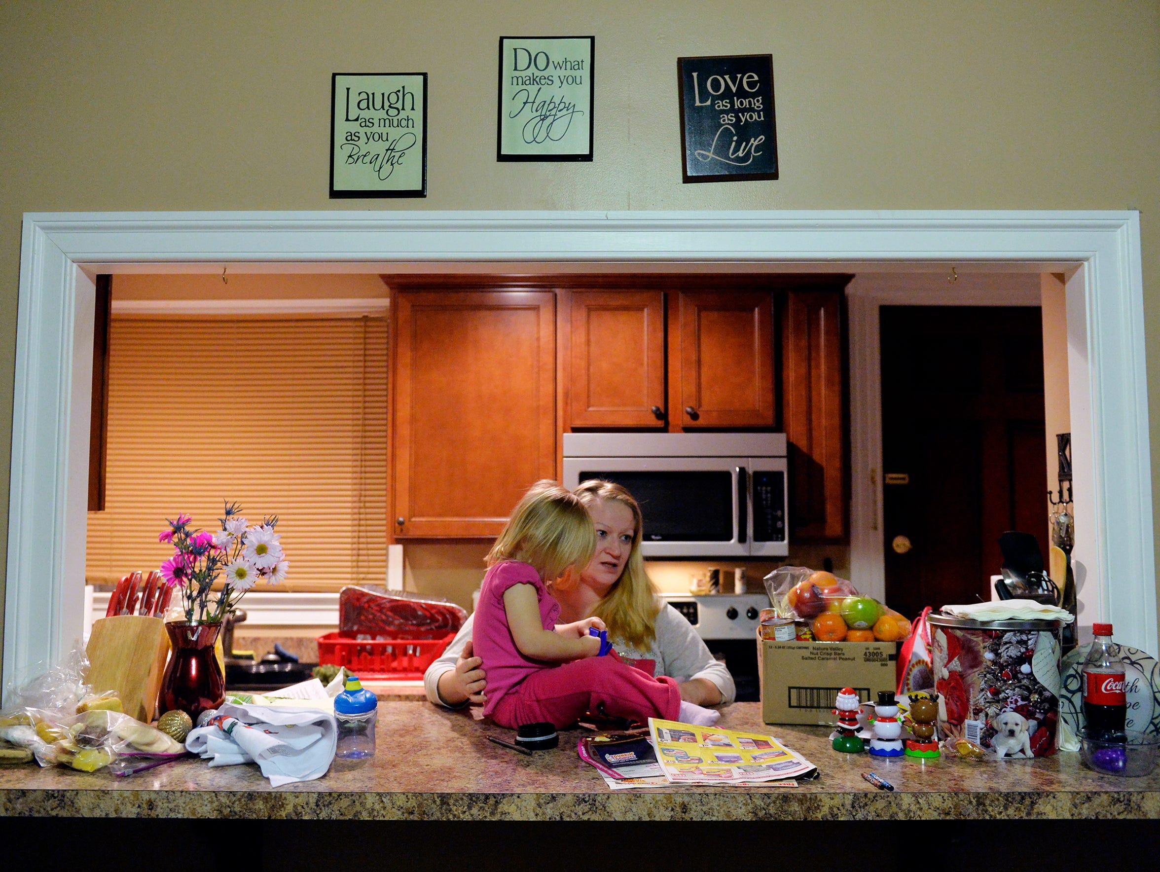 Melissa Rosenberry sits her daughter Arabella, 2, on